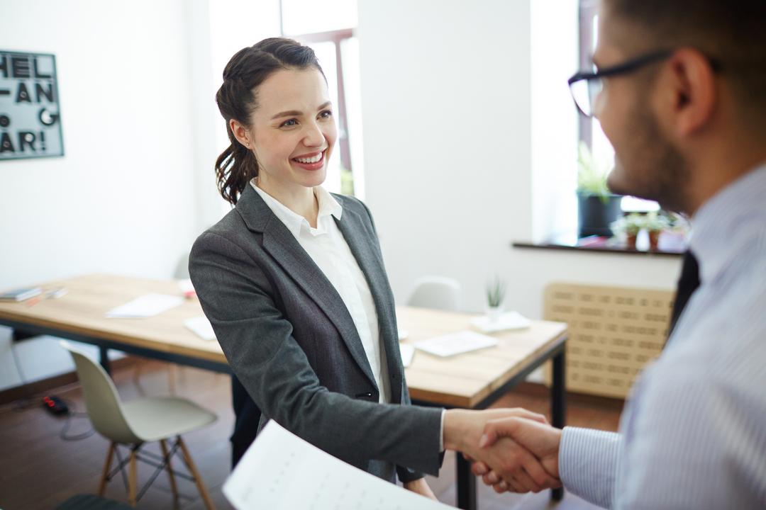 Recrutamento estratégico: entrevistadora e candidato apertam as mãos.