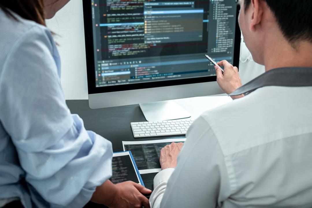 Contratar um desenvolvedor: dev explica código para colega de trabalho.