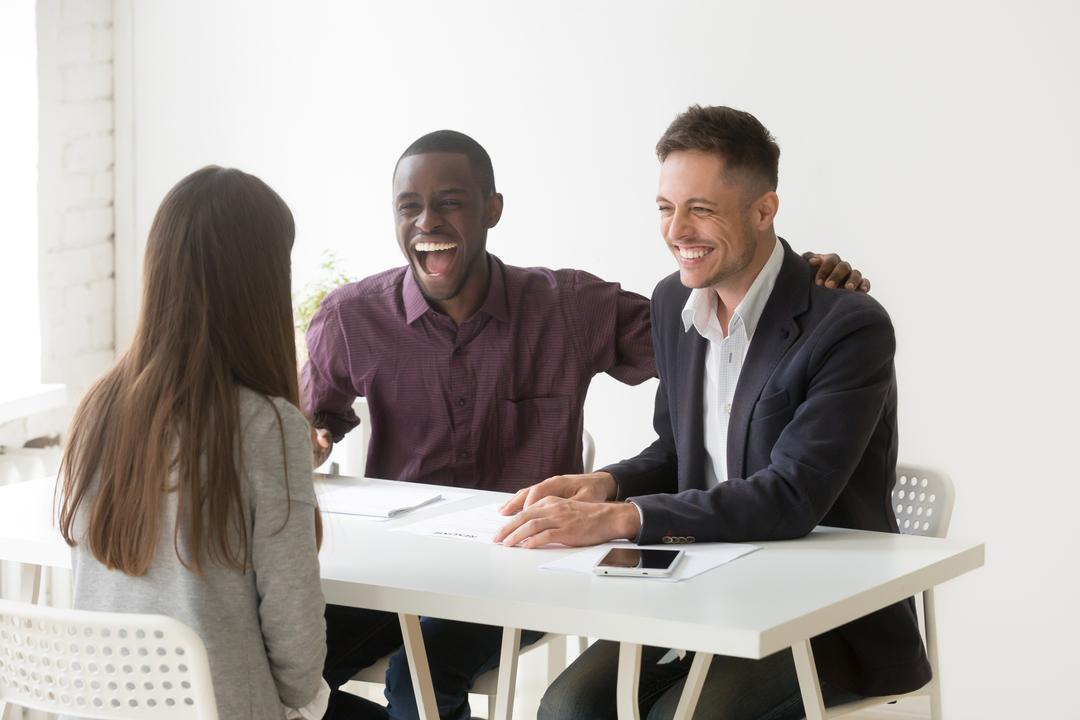 Marketing de recrutamento: recrutadores entrevistam pessoa alegremente.